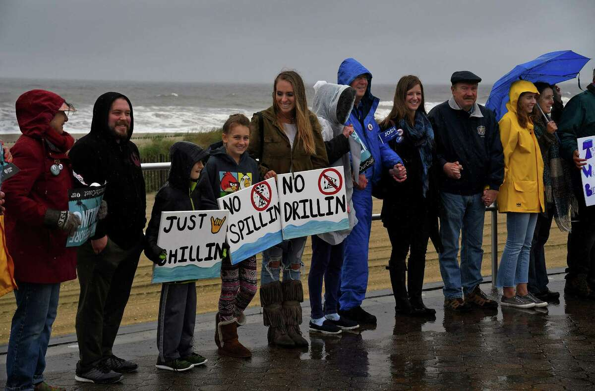 """Members of several environmental groups, along with local and state politicians, join a """"Hands Across the Sand"""" event in Bradley Beach, N.J., showing their opposition to offshore drilling and support of a clean-energy economy."""
