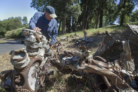 In a May 21, 2018 photo, Phil Boczanowski, developer of the property on Palomar Mountain, kneels at the memorial site on resident Mike LaPlant's lot on Palomar Mountain, with one of the radial engines from one of the planes that crashed on May 30, 1944. A group of dedicated researchers last month paid tribute to the fallen Navy fliers with a bronze memorial near the crash site atop Palomar Mountain. (John Gibbins/The San Diego Union-Tribune via AP)