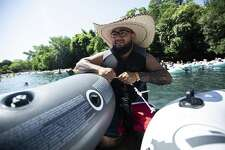 Robert Rodriguez works on securing some tubes together as he and his family prepare to tube down the Comal River at Prince Solms Park in New Braunfels, Texas on May 27, 2018.