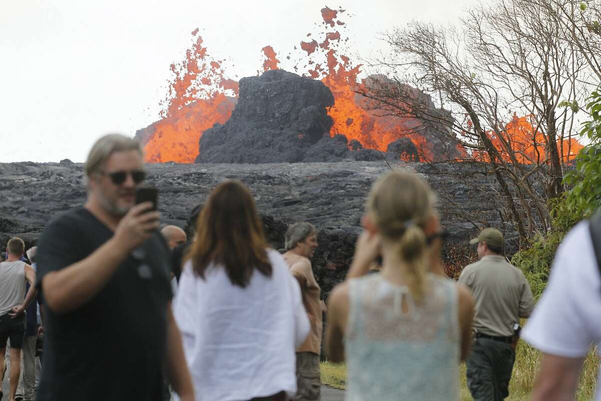 Area residents, the media and national guard flock Saturday, May 26, 2018, to what is now the end of Leilani Avenue to take in the fiery show at fissures 2, 7 and 8 of the Kilauea volcano near Pahoa. (George F. Lee/The Honolulu Advertiser via AP)
