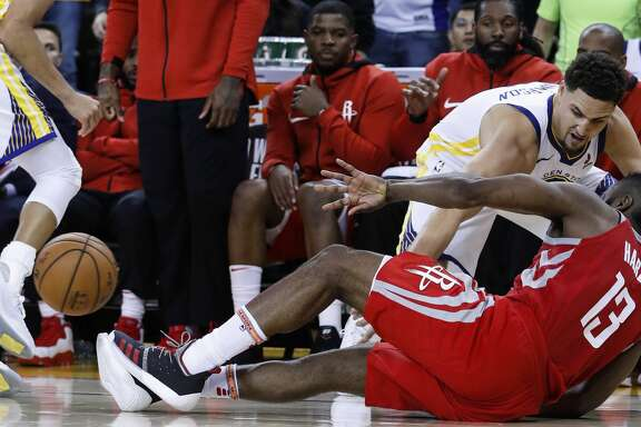 Houston Rockets guard James Harden (13) loses the basketball as he falls to the floor working against Golden State Warriors guard Klay Thompson (11) and guard Stephen Curry (30) during the second half of Game 6 of the NBA Western Conference Finals at Oracle Arena, Saturday, May 26, 2018, in Oakland.  ( Karen Warren  / Houston Chronicle )