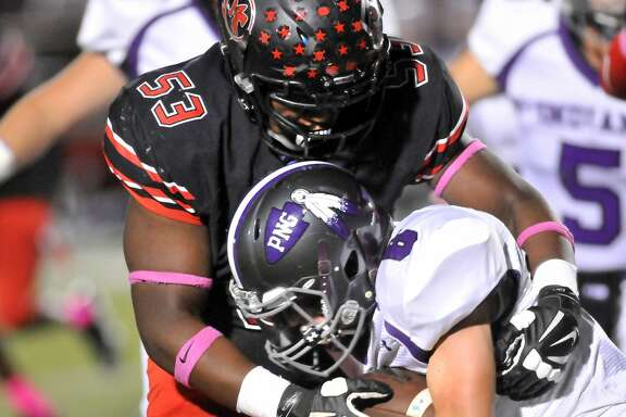 Memorial's DaJuan McMillan latches onto Port Neches-Groves' Preston Hughes before bringing him down in the first quarter of their game Friday night at Memorial Stadium in Port Arthur. (Mike Tobias/The Enterprise)