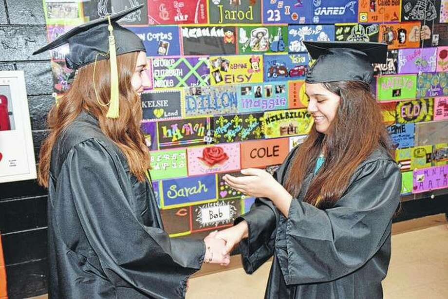 Beth Warden and Xenia Perez practice shaking hands and accepting their diplomas while waiting to enter Sunday's graduation ceremony. Photo:       By David Blanchette | For The Journal-Courier
