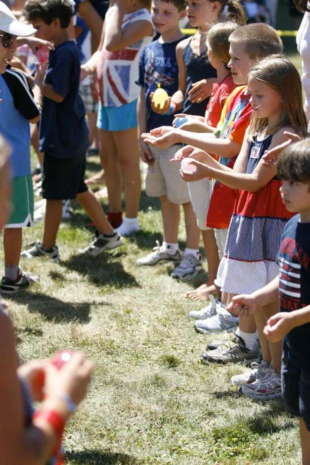 Children line up to compete in a water-balloon toss during the Pequot Library's Independence Day festivities in Southport on Sunday, July 4, 2010. Photo: Laura Buckman / Connecticut Post