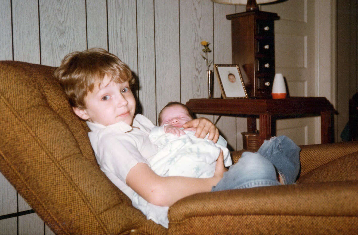 1. I have a younger sister and a younger brother. I am the only one without a tattoo and I'm the only one who didn't choose law enforcement as a career path. This is one of my favorite photos. In it, I'm holding my brother shortly after he was born.