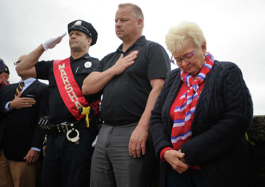 Judy Smarz Douglas, sister of deceased World War 2 veteran Lt. John Smarz, bows her head during the wreath laying ceremony in his honor during the annual Derby-Shelton Memorial Day Parade in Derby, Conn. on Monday, May 28, 2018. Derby Mayor Rich Dziekan is at center.