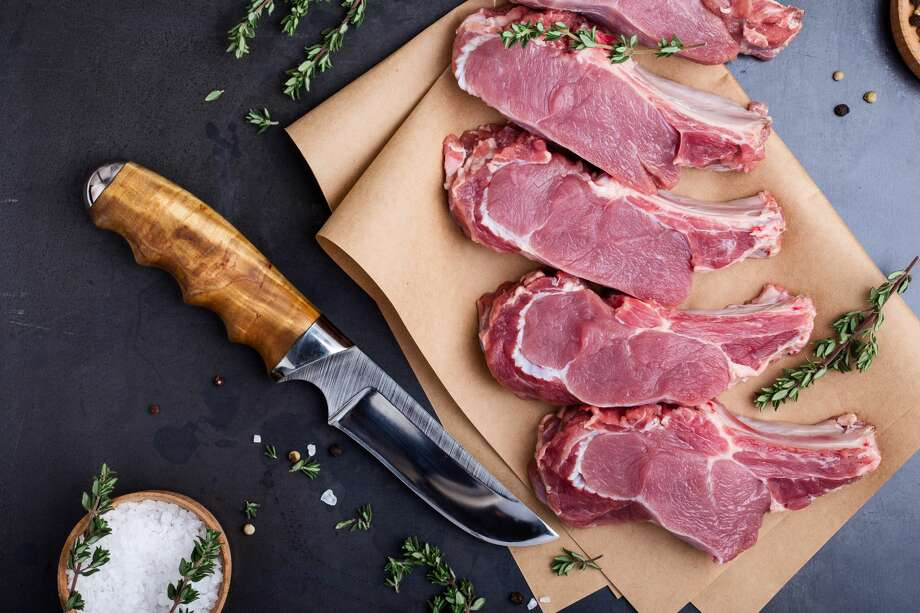 Raw organic veal steaks  on craft paper with herbs over  blue dark background. Top view Photo: Istetiana/Getty Images
