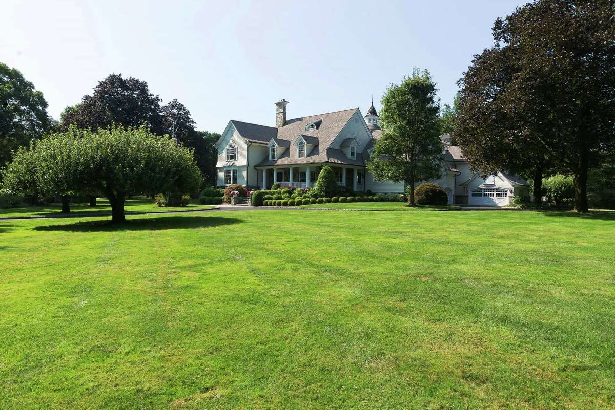 The custom clapboard and stone colonial house at 499 Silvermine Road sits on a two-acre level property and has a wealth of amenities for indoor-outdoor living.