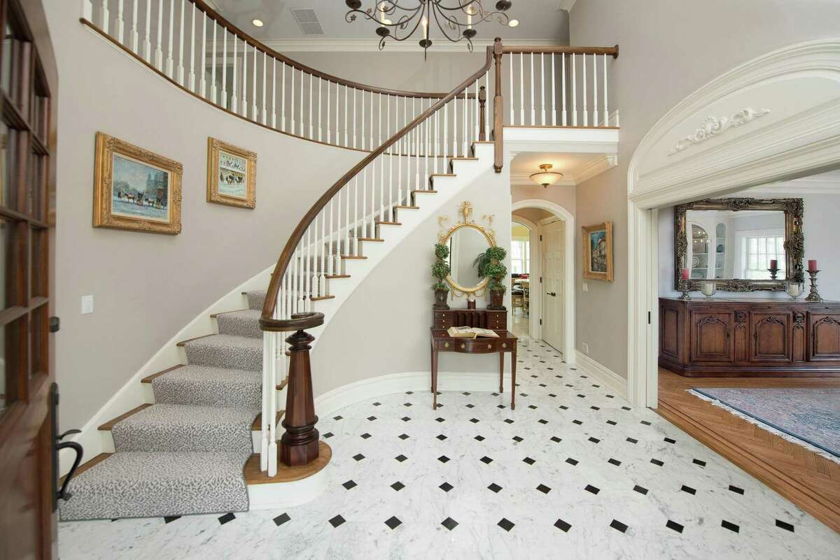 The two-story entrance foyer has marble flooring, curved staircase and ornamented entablature above the entranceways into the formal living and dining rooms.