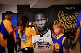 Warriors fans pass a photo of Kevin Durant in the hallway of Oracle Arena ahead of Game 4 of the Western Conference finals between the Golden State Warriors and the Houston Rockets in Oakland, California, on Tuesday, May 22, 2018.