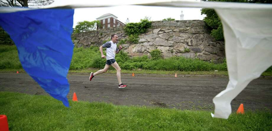 Stuart Allen, 55, of Greenwich, Conn., finishes the Jim Fixx Greenwich Memorial Day Five Mile Road Race in Greenwich, Conn., on Monday, May 28, 2018. Photo: Lindsay Perry / For Hearst Connecticut Media / Greenwich Time Freelance