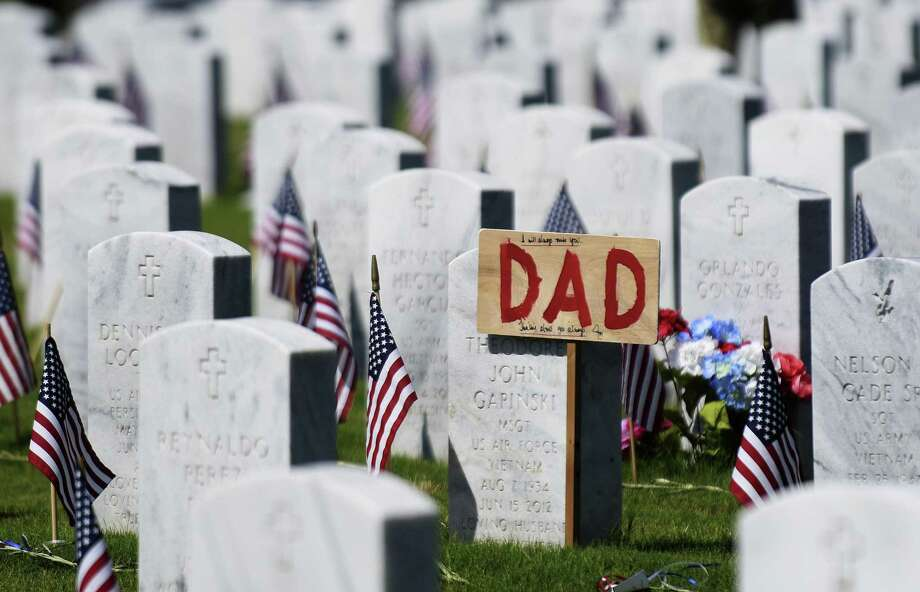 Fort Sam Houston National Cemetery honors service members with American flags — and families add personal touches. Photo: Staff File Photos / San Antonio Express-News