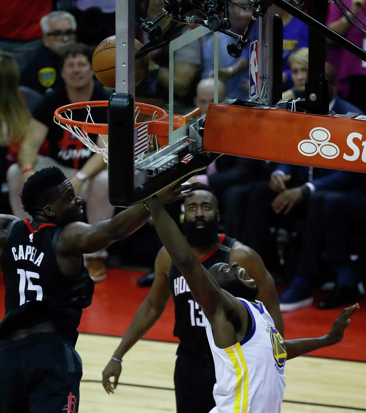 Golden State Warriors forward Draymond Green (23) tries to shoot around Houston Rockets center Clint Capela (15) during the first half of Game 7 of an NBA Western Conference finals at Toytota Center, May 28, 2018, in Houston.