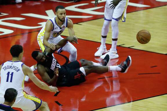 Houston Rockets guard James Harden (13) hits the ground guarded by Golden State Warriors guard Stephen Curry (30) during the first half of Game 7 of an NBA Western Conference finals at Toytota Center, May 28, 2018, in Houston.