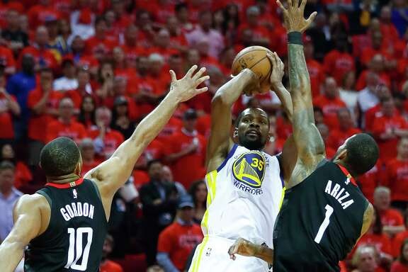 Golden State Warriors forward Kevin Durant (35) shoots from between Houston Rockets guard Eric Gordon (10) and forward Trevor Ariza (1) during the second half of Game 7 of the NBA Western Conference Finals at Toyota Center on Monday, May 28, 2018, in Houston.