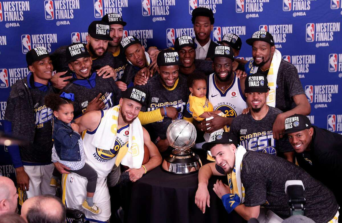 The Warriors lean in to get a team photo with the Western Conference Trophy after they defeated the Houston Rockets in Game 7 of the Western Conference Finals 101-92 to advance to the NBA Finals at the Toyota Center in Houston, Texas, on Monday, May 28, 2018.