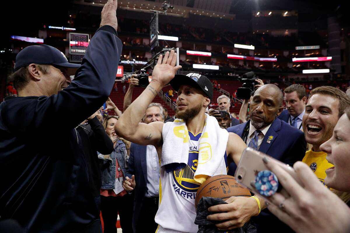 Stephen Curry high fives Tony Robbins after the Golden State Warriors defeated the Houston Rockets in Game 7 of the Western Conference Finals 101-92 to advance to the NBA Finals at the Toyota Center in Houston, Texas, on Monday, May 28, 2018.