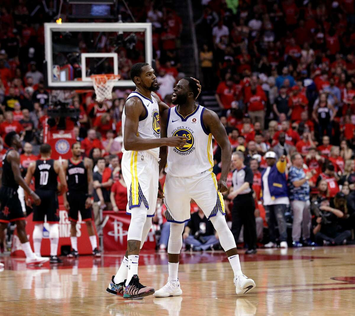Kevin Durant (35) and Draymond Green (23) celebrate in the final seconds of the fourth quarter as the Golden State Warriors defeated the Houston Rockets in Game 7 of the Western Conference Finals 101-92 to advance to the NBA Finals at the Toyota Center in Houston, Texas, on Monday, May 28, 2018.