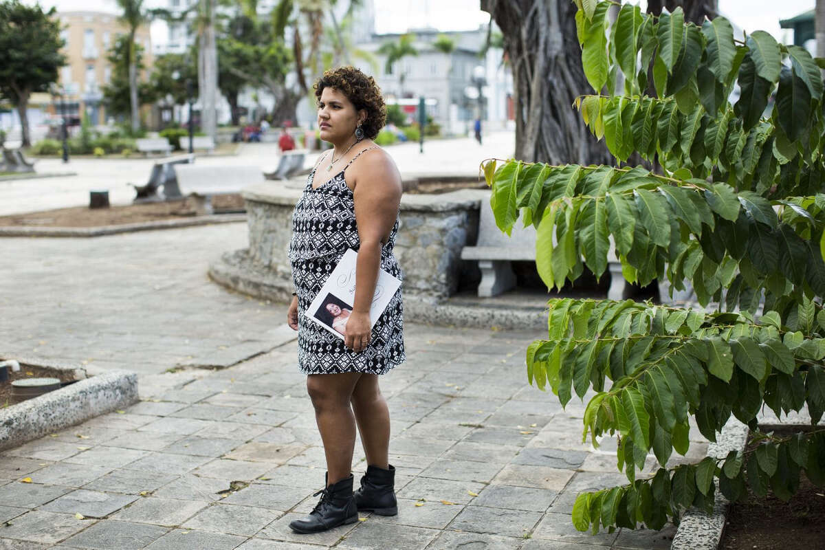 Miliana Montanez, 29, poses for a portrait with a memorial book for her mother in Caguas, Puerto Rico. Montanez's mother, Ivette Leon, died weeks after Hurricane Maria hit the island, something her family says was the result of crippled infrastructure.