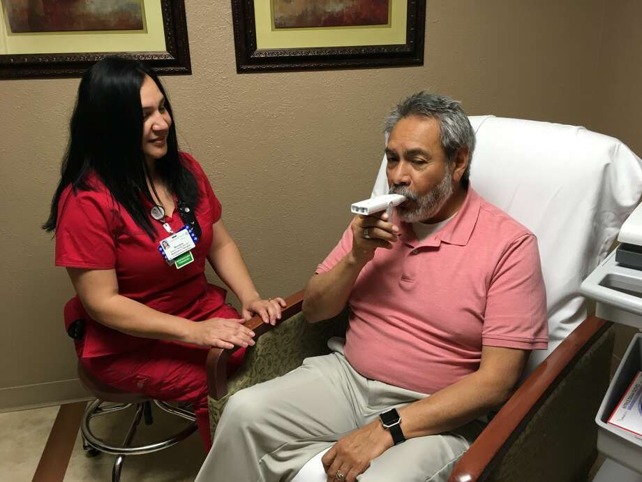 Covenant Health Plainview Respiratory Therapist Bernice Camarillo works with Juan Escamilla to use a Peak Flow Meter to measure his lung capacity. Photo: Homer Marquez/Covenant Plainview