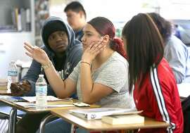 Castlemont High School seniors Amoy Tomlin (left), 17 years old, America Sanchez (middle), 17 years old, and Cynthia Galvan (right), 17 years old, take an English 4 class on Tuesday, May 8, 2018 in Oakland, Calif.  District officials released a report today on the impact of charter schools on the district at Castlemont High School.