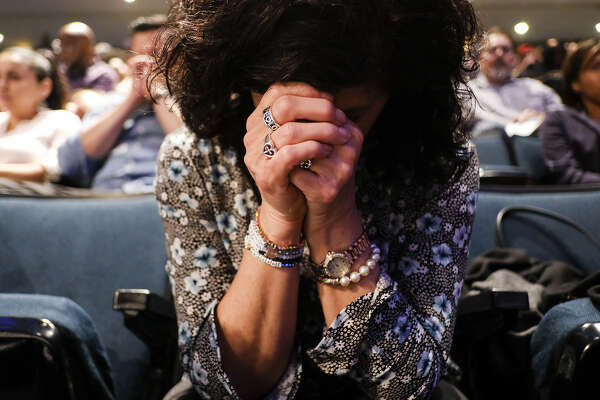 Vickie McGinty bows her head in prayer as she attends a Wednesday service at Lakewood Church.