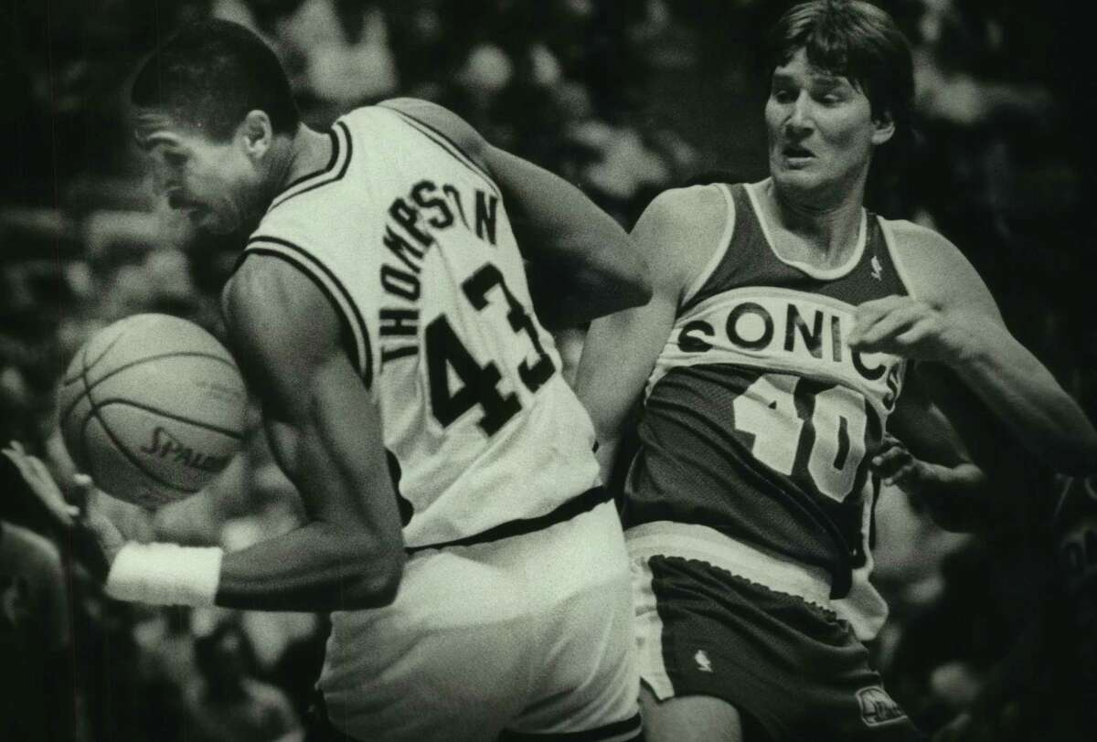 Spurs forward Mychal Thompson is defended by the Seattle SuperSonics' Russ Schoene in 1986.