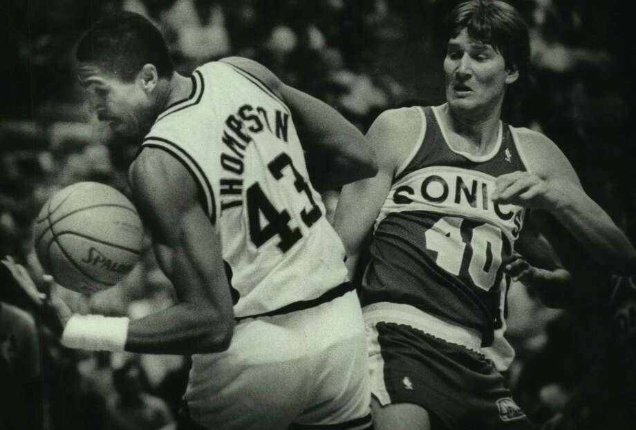 Spurs forward Mychal Thompson is defended by the Seattle SuperSonics' Russ Schoene in 1986. Photo: John Davenport / San Antonio Express-News / San Antonio Express-News
