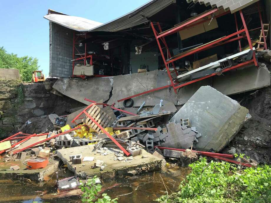 A storage garage attached to the rear of Abacore Electric, a factory building at 281 Canal Street in Shelton, Conn. fell, spilling its contents into the Housatonic River on Tuesday, May 29, 2018. Photo: Brian A. Pounds, Hearst Connecticut Media / Connecticut Post