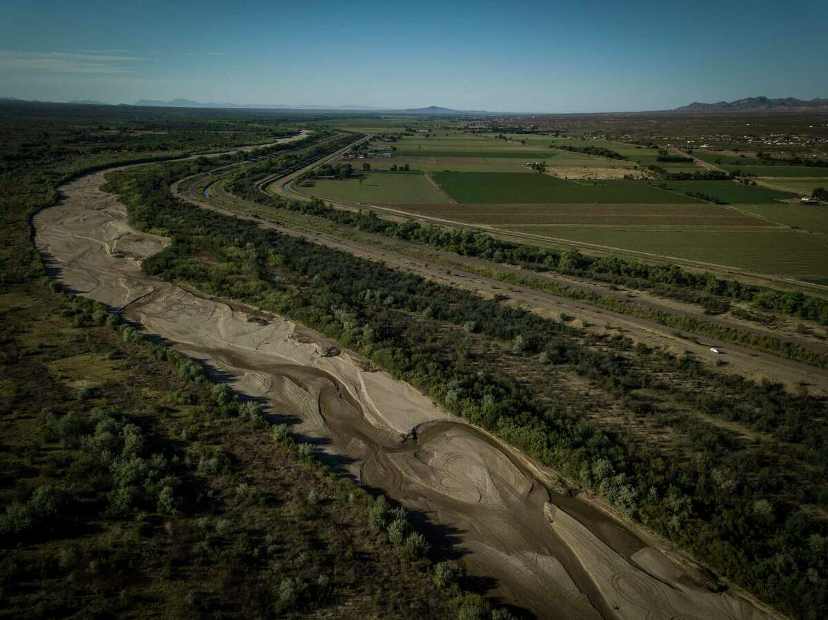 At left, the largely dry Rio Grande, and at right, irrigation canals run along farmland, near Socorro, N.M., May 10 ,2018. Even in a good year, much of the Rio Grande is diverted for irrigation, but it's only May, and the river is already turning to sand. (Josh Haner/The New York Times)