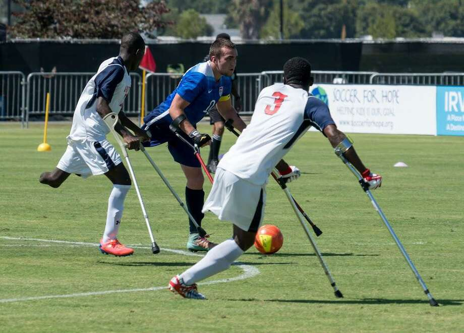 USA's Nicolai Calbria, center, keeps his eyes downfield while controlling the ball. The American national amputee team will host England and Haiti in a tournament this weekend in The Woodlands. Photo: Submitted / Carl Calabria