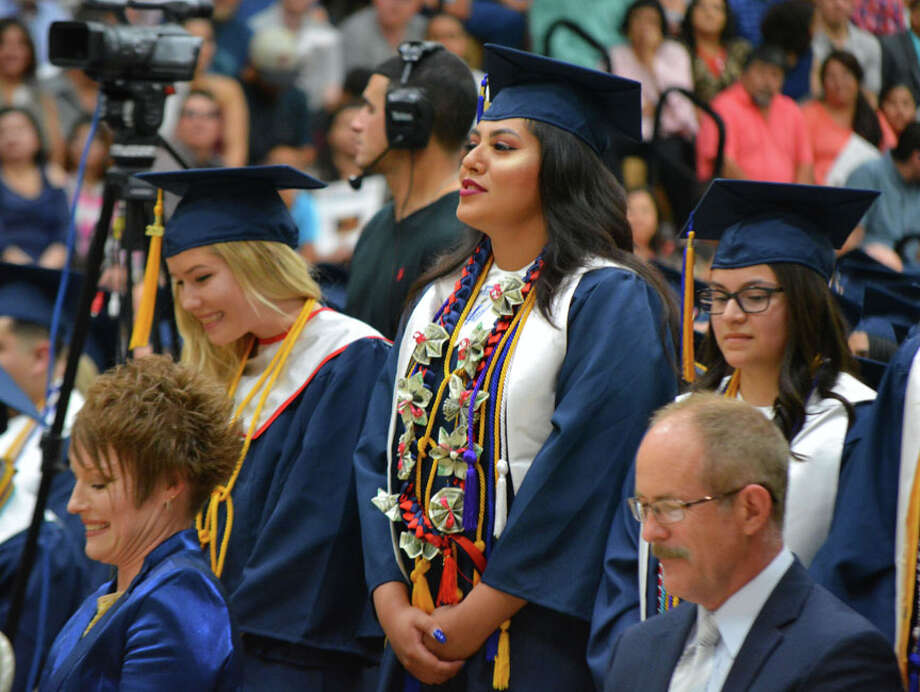 Flanked by fellow Plainview High honor graduates Liberty Crawford (left) and Larissa Anne DeLaRosa (right), Crusita Antonia Cruz-Chavez sports a leis crafted from folded American currency at Friday's Plainview High School Commencement exercises. Seated in front of the trio are Brandy Merrick, PISD executive director for human resource services, and Dr. Brent Richburg, executive director for technology and information system services. Photo: Doug McDonough/Plainview Herald