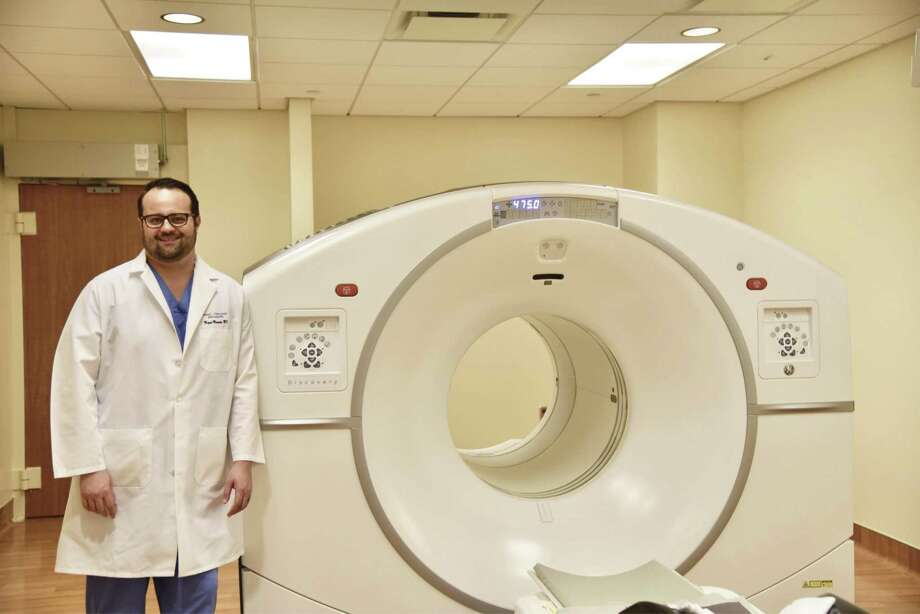 Dr. Miguel Mercado, with Texas Urology Specialists and Houston Methodist Physicians' Alliance for Quality, stands next to PET/CT scanning machine at Houston Methodist The Woodlands Hospital, which along with an Axumin injection can detect early stages of recurring prostate cancer in men with elevated PSA levels.