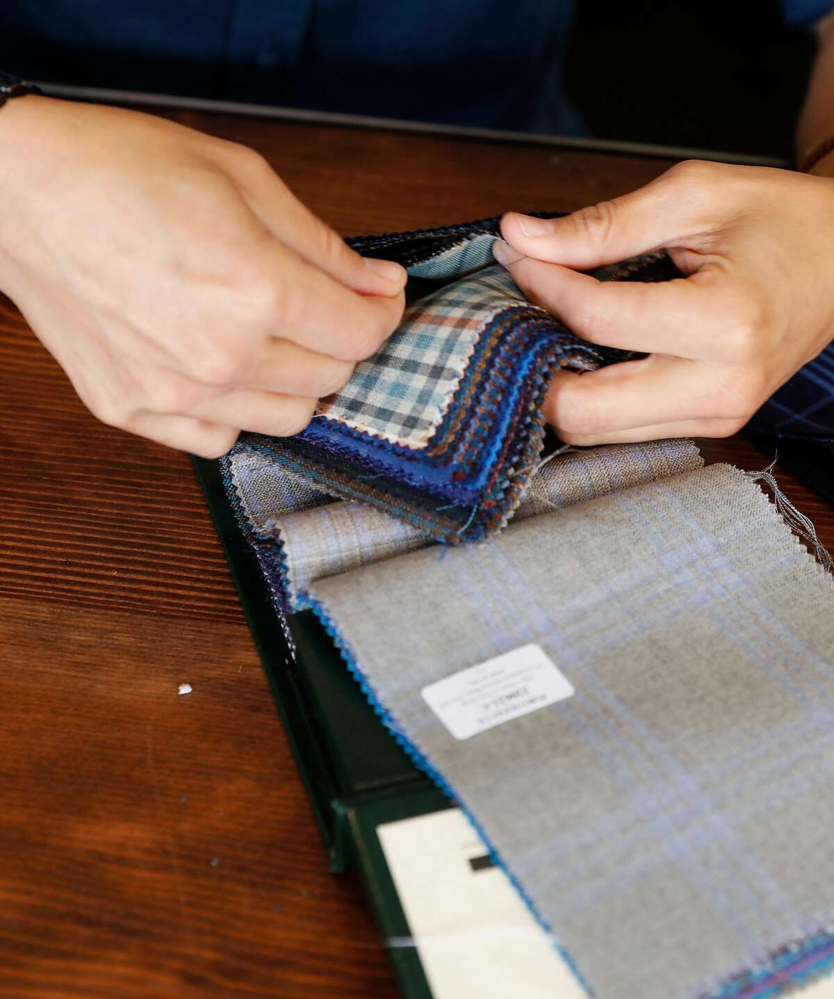 Riley Hewko goes through material swatches at Kipper Clothiers on Friday, May 25, 2018 in San Francisco, Calif.