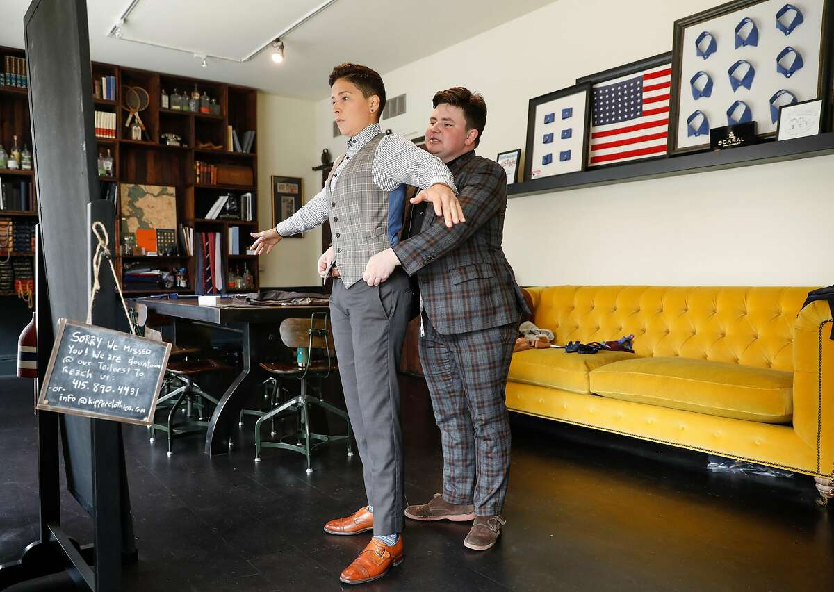 Erin Berg, co-founder of Kipper Clothiers, right, measures client and attorney at the Transgender Law Center, Riley Hewko, on Friday, May 25, 2018 in San Francisco, Calif.