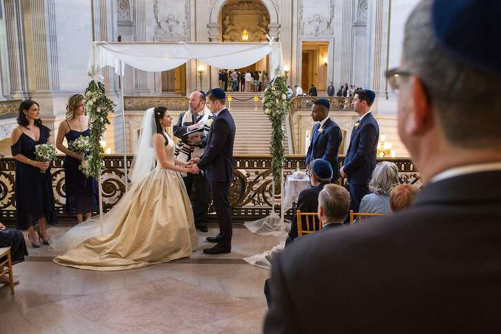 Lauren Koblitz and Aaron Shapiro stand under chuppah holding hands during their wedding ceremony on the balcony of City Hall on Friday, May 11, 2018. San Francisco Calif.