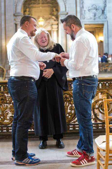 Oliver Meier (left) and Andreas Neumann of Germany exchange rings during their wedding ceremony on the balcony of City Hall. Photo: Jana Asenbrennerova / Special To The Chronicle