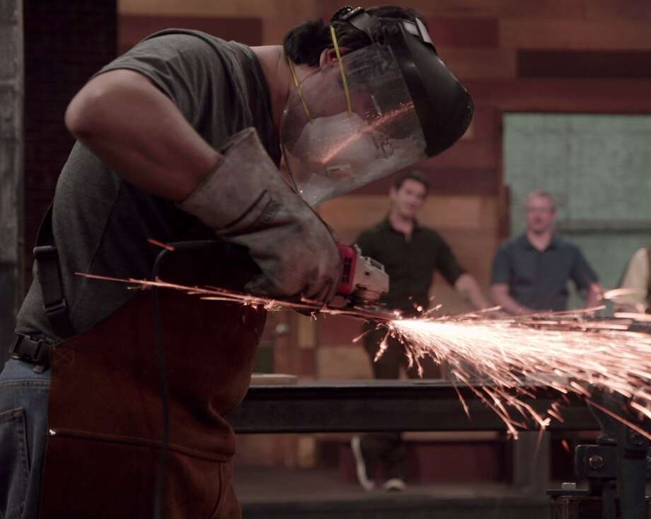 "Contestant Alex Ruiz grinds a blade on History's ""Forged In Fire."" The Horseman's Axe episode airs tonight."