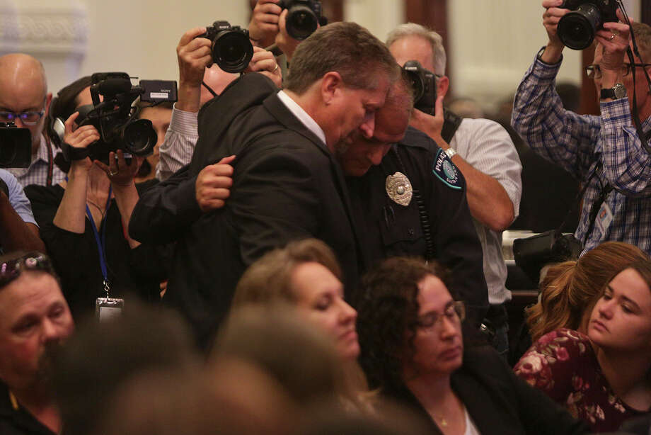Scot Rice, left, embraces officer Johnny Banda, after Rice read a statement about his wife, who was shot and wounded during the shooting at Sante Fe High School, and Banda helping to save her life, during a roundtable with Gov. Greg Abbott concerning school security at the Texas State Capitol on Thursday, May 24, 2018. Photo: Lisa Krantz/SAN ANTONIO EXPRESS-NEWS / SAN ANTONIO EXPRESS-NEWS
