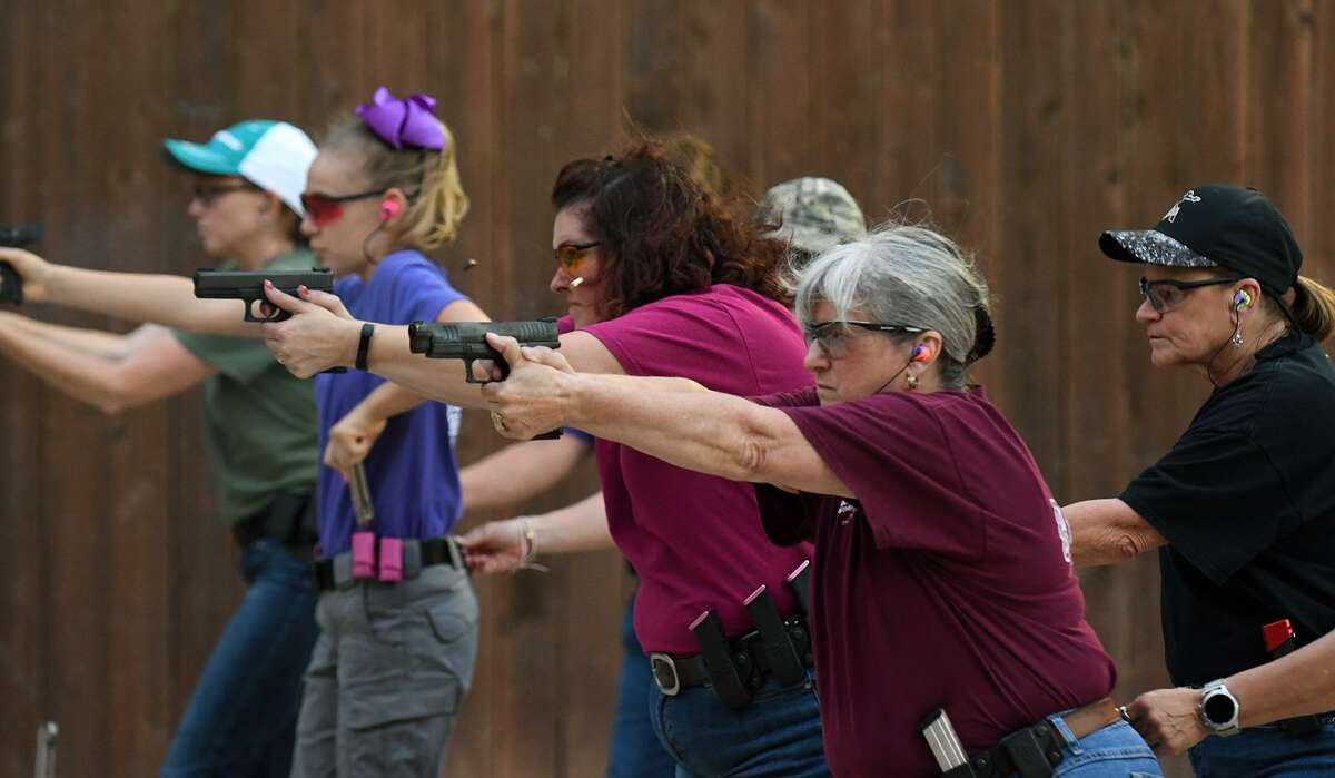 """Members of the Cypress chapter of """"A Girl and a Gun"""" women's shooting social group, including Cindy Garza, center, of Tomball, practice utilizing cover during a shooting drill on the firing line at Hot Wells Shooting Range in Cypress on May 15, 2018. (Jerry Baker/For the Chronicle)"""