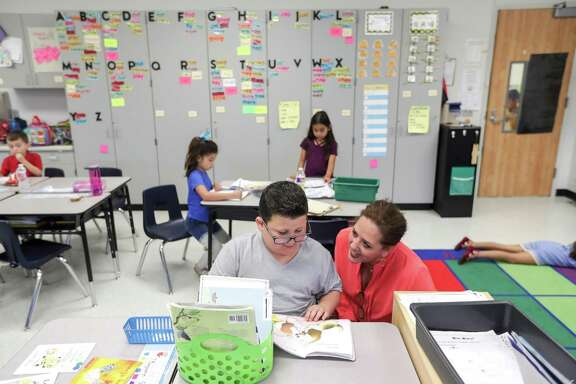 Jennifer Walker, front right, the principal of Lawhon Elementary School in Pearland, works with Benjamin Guerrera, 6, during his first grade class.