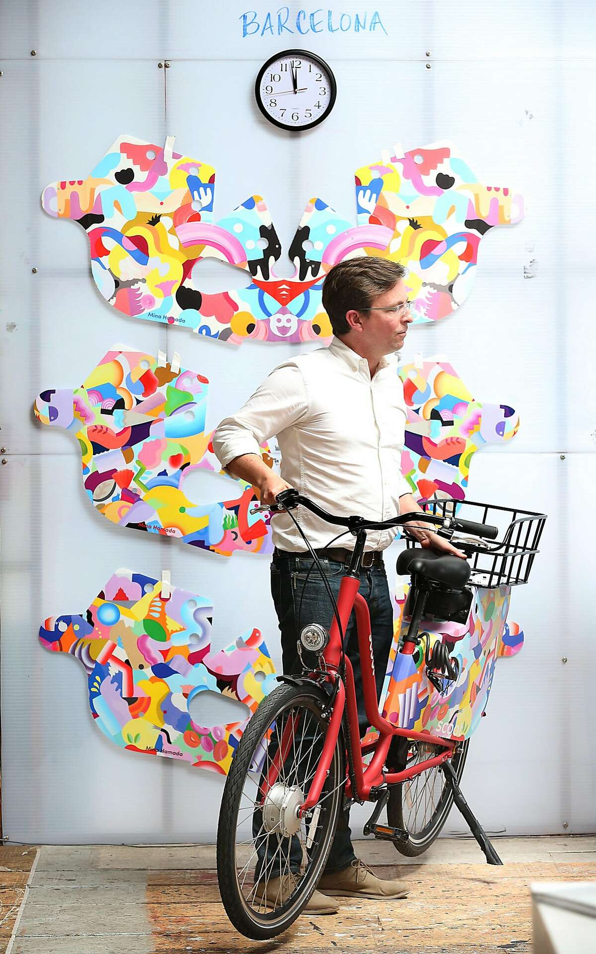 CEO Michael Keating of Scoot, a San Francisco-based shared electric mobility company, shows artwork that will be included on their bikes in Barcelona on Thursday, May 24, 2018 in San Francisco, Calif.