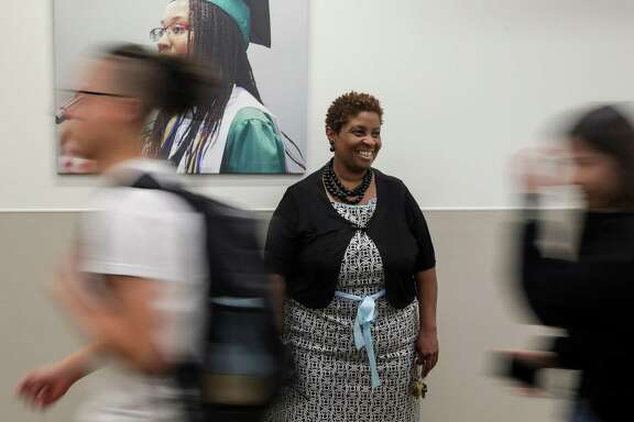 Phyllis Cormier, principal at Victory Early College High School, smiles as she watches students during a passing period.