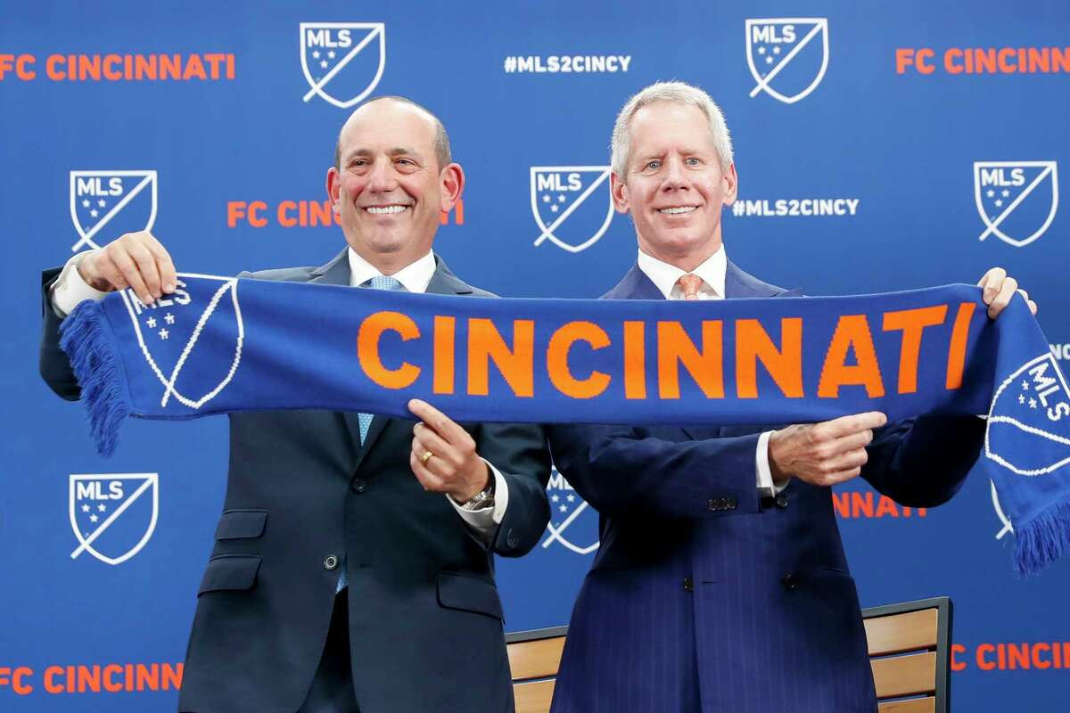 Major League Soccer Commissioner Don Garber, left, and FC Cincinnati owner Carl Lindner III, right, hold a scarf after announcing the addition of FC Cincinnati as an expansion team, Tuesday, May 29, 2018, at Rhinegeist Brewery in Cincinnati. FC Cincinnati has set attendance records in its three seasons in the United Soccer League and plans to have a soccer-only stadium ready for the 2021 season. The announcement on Tuesday brings MLS a step closer to its goal of a 28-team league. The latest round of expansion will bring it to 26 teams. (AP Photo/John Minchillo)