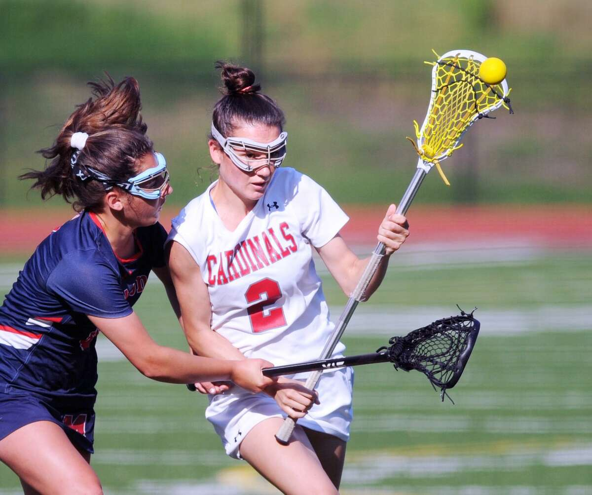 Paige Finneran (#2), right, of Greenwich, shoots during the girls high school Class L lacrosse playoff match between Greenwich High School and Brien McMahon High School at Greenwich, Conn., Tuesday, May 29, 2018.