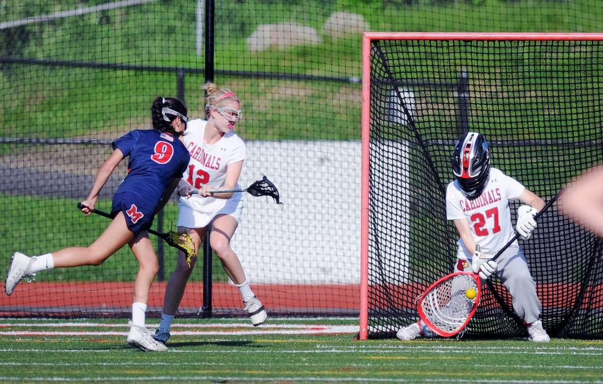 Greenwich goalie Sloane Loveless stops a shot by McMahon's Anna Makover during their game Tuesday in Greenwich. Defending for Greenwich at center is Sailor Jiranek.