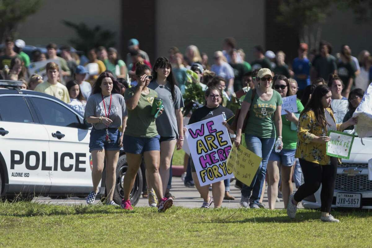 Alvin High School students and staff walk to the Santa Fe High School shooting memorial on Tuesday after welcoming Santa Fe students with flowers and supportive signs back to campus 11 days after a shooting that killed eight students and two teachers. Tuesday, May 29, 2018, in Santa Fe. ( Marie D. De Jesus / Houston Chronicle )