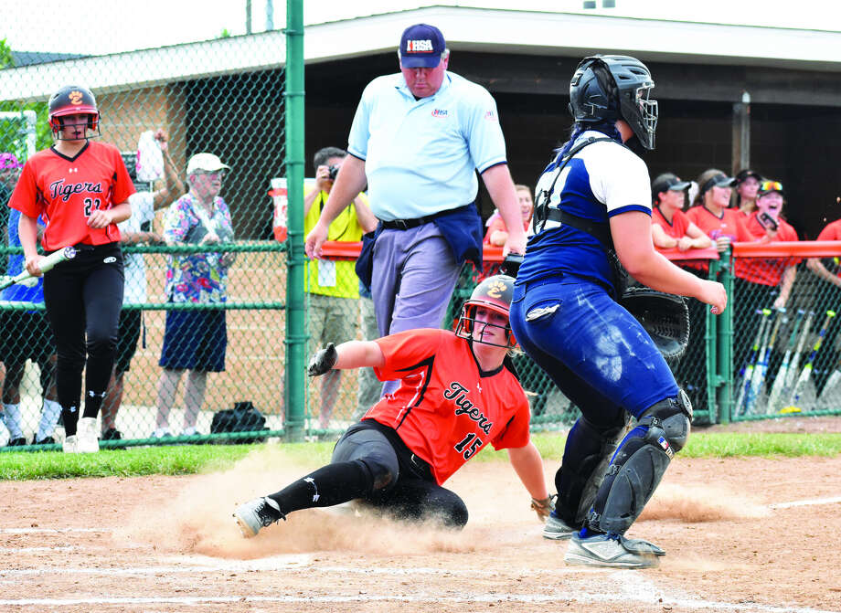 Edwardsville's Anna Burke slides safely into home as Belleville East catcher Alexandra Boze waits for a throw from the outfield during the first inning of Tuesday's game inside the District 7 Sports Complex.