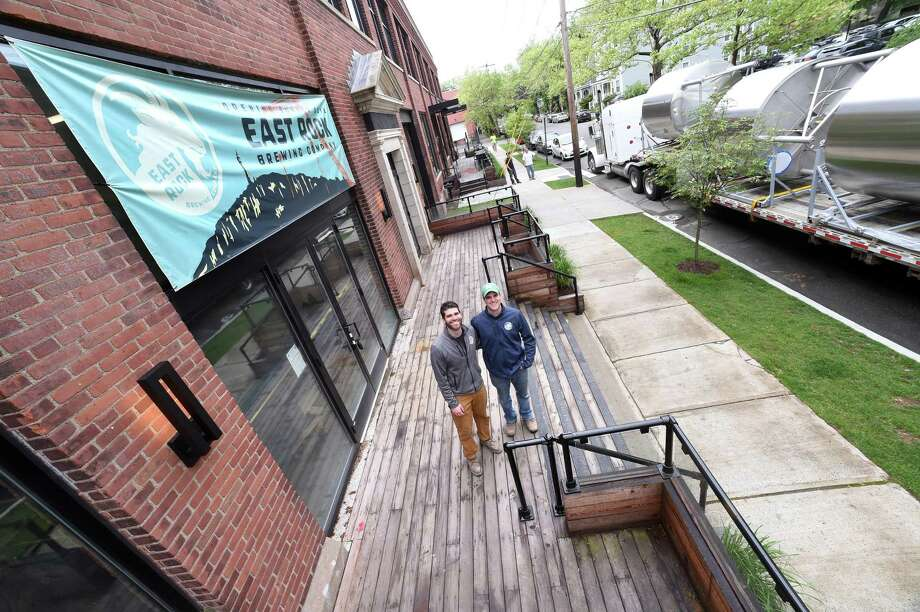 East Rock Brewing Company co-owners and brothers Ti , left, and Shaun Wilson outside the brewery on Nicoll Street in New Haven as equipment is delivered recently. Photo: Arnold Gold / Hearst Connecticut Media / New Haven Register