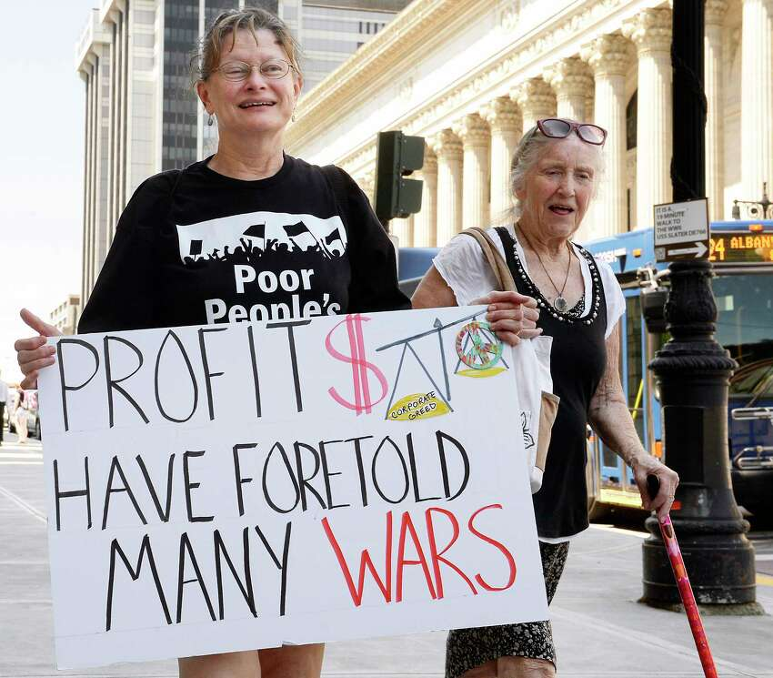Cathy Morton of Syracuse carries a sign into the Capitol for a Poor People's Campaign Tuesday May 29, 2018 in Albany, NY. (John Carl D'Annibale/Times Union)